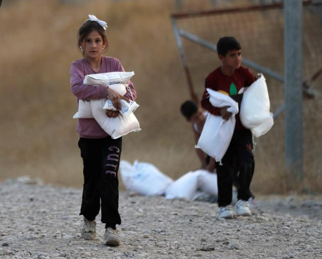 Children, who were displaced by the Turkish military operation in northeastern Syria, carry food supplies at the Bardarash refugee camp, north of Mosul, Iraq. (AP Photo/Hussein Malla)