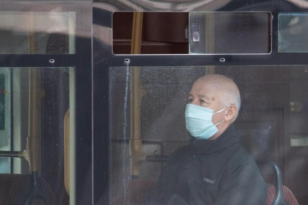 A passenger wearing a protective face mask on a bus (Dominic Lipinski/PA)