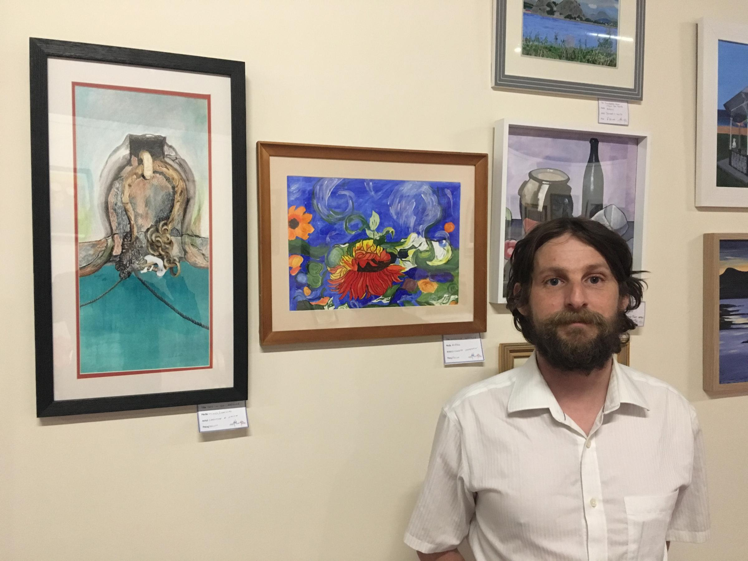 Allan Rutherford in front of some of Faifley Art Group's work
