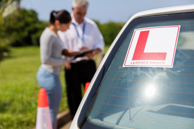 learner driver sign on a car with student and instructor standing behind.